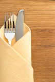 Knife and fork at napkin on wood Stock Photos