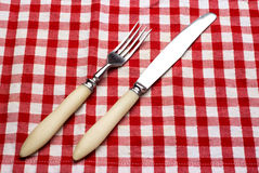 Knife and fork at napkin on wooden Stock Photos
