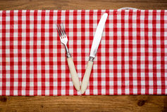 Knife and fork at napkin on wooden Stock Photography