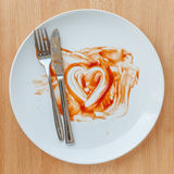 Knife and fork over in finish plate and heart shape ketchup. Royalty Free Stock Photos