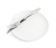 Knife and fork over the plate isolated Royalty Free Stock Photo