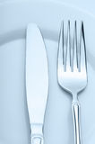 Knife and fork on a plate Stock Photography