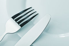 Knife and fork on a plate Royalty Free Stock Photos