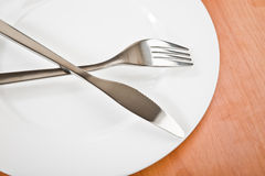 Knife and fork on plate Stock Photography