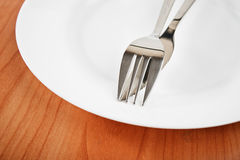 Knife and fork on plate Stock Photos