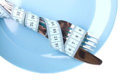 Knife and fork on plate. Knife and fork bound with measure tape on a plate Stock Images