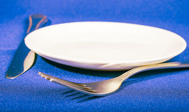 Knife, fork  and plate  on blue tablecloth Royalty Free Stock Photography