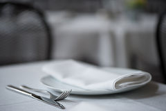 Knife, fork, plate and folded napkin upon white table cloth. Stock Photography
