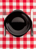 Knife and fork at plate on napkin Stock Photos
