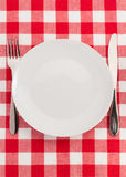 Knife and fork at plate on napkin Royalty Free Stock Images