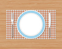 Knife, fork, plate, red checked cloth, wooden desk Stock Image