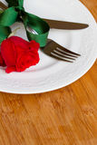 Knife and fork on plate  with rose Stock Image