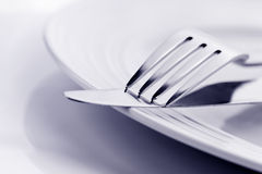 Knife and Fork on Plate Soft Focus. Knife and fork on white plate, in soft focus Stock Photo