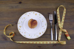 Knife with a fork, plate, tape measure and peach on a wooden bac Royalty Free Stock Photos