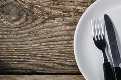 Knife and fork on a plate Stock Photos