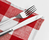 Knife and fork on red checked tablecloth Royalty Free Stock Photo