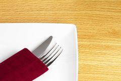 Knife and fork in red napkin on plate Stock Photos