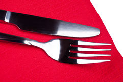 Knife and fork on red tablecloth Stock Images