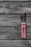 Knife and fork in red white checkered on wooden background. Royalty Free Stock Photography