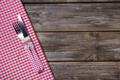 Knife and fork in red white checkered on wooden background. Stock Images