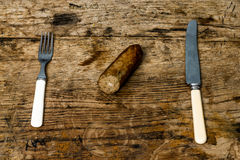 Knife, fork and sausage on wooden table Royalty Free Stock Photos
