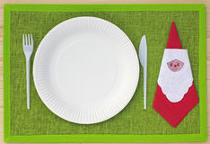Knife, fork, serviette and plates of cardboard on green place set Stock Photos