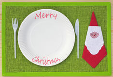Knife, fork, serviette and plates of cardboard on green place set Stock Image
