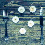 Knife and fork set on a wooden vintage table. Is surrounded of candles Royalty Free Stock Photos