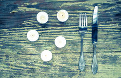 Knife and fork set on a wooden vintage table. Is surrounded of candles Stock Photo