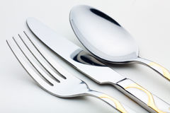 Knife, fork, spoon. A set of spoons, forks and knives lying on the white tablecloth. Close-up royalty free stock photos