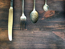 Knife, fork and spoon on a brown wooden background Stock Photos