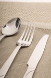 Knife, fork and spoon with linen serviette Stock Photography