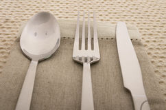 Knife, fork and spoon with linen serviette Stock Photos