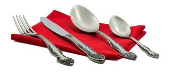 Knife, fork, spoon on red silk Stock Photos