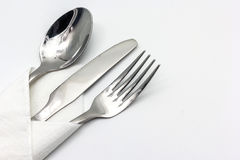Knife, fork and spoon with serviette, isolated on the white background Stock Photos