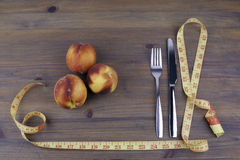 Knife with a fork, tape measure and peaches on a wooden backgrou Stock Photos