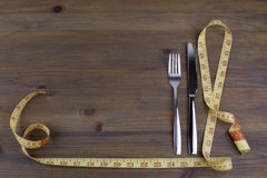 Knife with a fork and tape measure on a wooden background Royalty Free Stock Photo