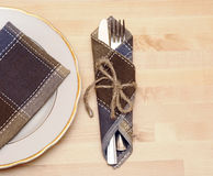 Knife and fork in textile napkin Stock Photos