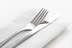 Knife and Fork on White Linen. Silver knife and fork on white linen napkin Stock Photos