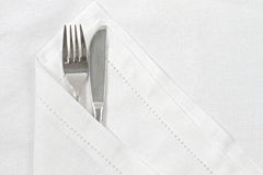 Knife and fork with white linen serviette Stock Photography