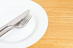Knife and fork on white plate Royalty Free Stock Photo