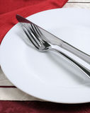 Knife and fork on a white plate Stock Photography