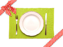 Knife, fork and white plate on a green napkin Stock Photos
