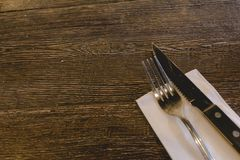Knife and fork on a wood table with white napkin royalty free stock image
