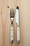 Knife and fork on wooden table Royalty Free Stock Photography