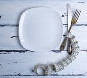 Knife with a fork wrapped in a measuring tape with a white squar. E ceramic plate, top view Stock Photography