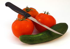 A knife and fresh vegetables tomato and cucumber. On white background, isolated Royalty Free Stock Images