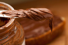 Knife full of sweet chocolate nougat spread on glass jar. Stock Photo