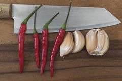 Knife, garlics and chillies on chopping board. Knife, garlics and chillies on wooden chopping board Royalty Free Stock Photos