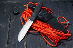 Knife of the German army. A military knife on an orange paracord cord. stock images